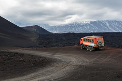 Expedition truck on mountain road near lava fields and volcanoes Stock Photos