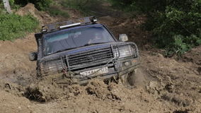 Expeditionary SUV riding though deep trench with dirty water and stucks. RUSSIA, ADYGEA, MEZMAI - MAY 8,2017: Expeditionary SUV with big wheels riding though stock footage