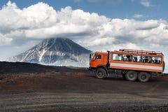 Expeditionlastbil på bergvägen på bakgrundsvolcanoes Royaltyfri Fotografi