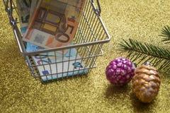 Expediture se relacionó con los días de fiesta/concepto/decoraciones, árbol de navidad y carro de la compra con el dinero euro fotos de archivo libres de regalías