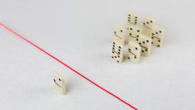 Expelled from the group, unable to cross the red line that separates them. Scene with group of domino. Concept of Stock Images