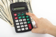 Expenses. A child calculating expenses on a calculator that stands on  a couple of dollars Royalty Free Stock Photos