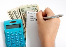 Expenses. Writing a list with a calculator and some money on the background royalty free stock photo