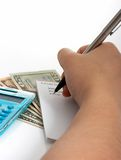 Expenses. Writing a list with a calculator and some money on the background Stock Image