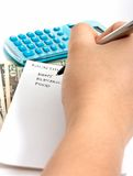Expenses. Writing a list with a calculator and some money on the background stock images