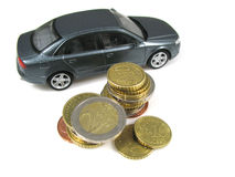 Expenses of driving a car. A car and some coins in the front stock photos