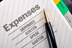 Daily expenses record. Expenses book page or record and a ball pen, shown as woking on expenses, cost, saving, charge, payout,  consumption, purchasing and other Stock Photos