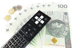 Expenses tv. TV remote control lies next to Polish money Royalty Free Stock Photos