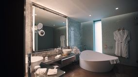 Expensive bathroom interior, huge mirror and tub, white towels pile