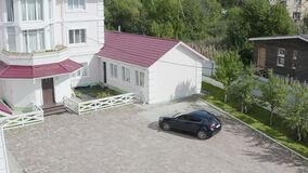 Expensive car at country cottage. Video. Top view of car arriving at large country cottage. Car with rich family came to