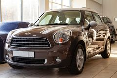 An expensive car, a female model of a mini cooper beige and gold color and a white roof polished and shiny is set up in a car stock image