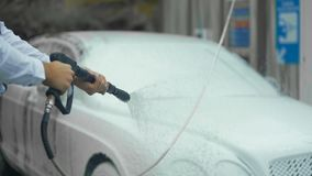 Expensive carwash, male dressed in suit washing car with cleaning foam, business. Stock footage stock video