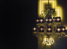 Expensive chic chandelier on black background. Chandelier. With warm glowing in dark interior, defocused. Chandelier with many lamps and intimate atmosphere royalty free stock images