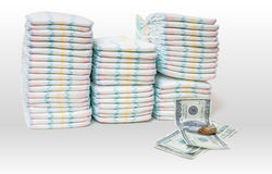 Expensive childcare. A pile of diapers and money on white background.  stock photos