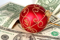 Expensive Christmas. Red Christmas orniment on a pile of money Royalty Free Stock Image