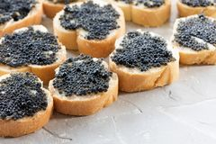 Expensive delicious black caviar white bread sandwich snack on w. Expensive delicious black caviar white bread sandwich snack on a wooden plate royalty free stock photography