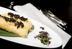 Expensive dish with black caviar. On black arranged table, closeup royalty free stock image