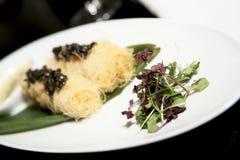 Expensive dish with black caviar. On black table, closeup stock image