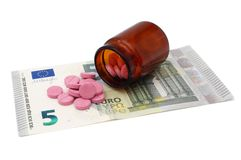 Expensive drugs concept with pills on money Stock Photos