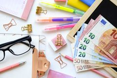 Investing time and money into education concept. Different school supplies, banknotes. Top view, close up. stock image