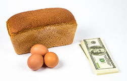 Expensive eggs, bread and dollars Royalty Free Stock Photos