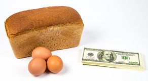 Expensive eggs, bread and money Stock Photo