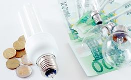 Expensive electricity. A concept of expensive electricity. Energy saving bulb with some coins and old bulbs with a lot of money for expenses Stock Image