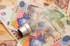 Expensive electricity. A new light bulb (focus on bulb) on South African money background Royalty Free Stock Photography