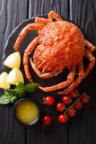 Expensive food: cooked whole crab spider with lemon and melted b. Utter close-up on the table. Vertical top view from above royalty free stock photo
