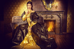 Expensive furnishings. Renaissance Style -  beautiful young woman in the lush expensive dress in an old palace interior. Vintage style. Fashion Stock Images