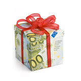 Expensive gift. A gift box covered in Euro banknotes with red colored ribbon applied stock photo