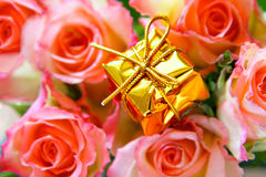Expensive gift and roses. Expensive gift close-up and rosebuds in the background out of focus Stock Photography