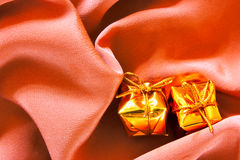 Expensive gifts. Over silk background with folds Stock Photos