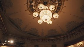 Expensive golden chandelier appears from behind dark drapes in concert hall stock video footage