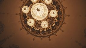 Expensive golden chandelier on concert hall ceiling with murals stock video footage