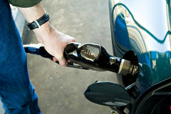 Expensive Gratification. Man filling up his fancy sports car with gas Stock Photo