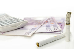 Expensive habit. Half burned cigarette with Euro money and calculator in background. Concept of expensive habit Stock Images