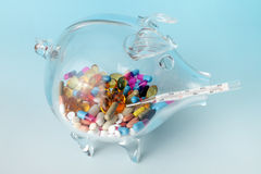 Expensive health. Glass piggy bank filled with medical pills and thermometer Royalty Free Stock Photography