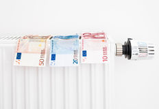Expensive heating costs. Heating costs concept with euro money hanging on a radiator Royalty Free Stock Photography