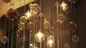 Expensive Large Chandelier Of Glass In A Restaurant Or Concert Hall. Chandelier Lighting In Hall, Bokeh, Glare, Glow