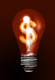 Expensive light bulb. A classic light bulb burning, with the dollar symbol into it Royalty Free Stock Photo