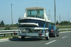 Expensive luxury car tows a ship. An expensive luxury car tows a ship in the motorway Royalty Free Stock Photo