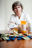 Expensive medication concept. Sad, stressed woman with medication and USD money on the table in front of her Royalty Free Stock Image