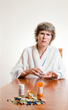 Expensive medication concept. Lady with prescription medication and money in-front of her. Expensive medication. Sad patient Royalty Free Stock Images