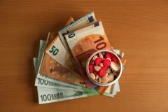 Expensive medication treatment. Various pills on the background of money. Expensive medication. Various pills amid money royalty free stock photo