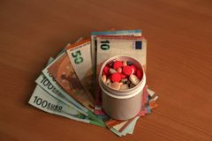 Expensive medication treatment. Various pills on the background of money. Expensive medication. Various pills amid money stock photography