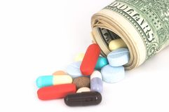 Expensive Medicine. Closeup Money rolled up with pills falling out, high cost, expensive healthcare Stock Photo