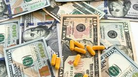 Expensive medicine. Pills of different colors on money background stock footage