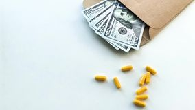 Expensive medicine. Pills of different colors and money on white table stock footage