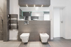 Expensive modern bathroom. Expensive shiny modern bathroom in marble tiles royalty free stock photos
